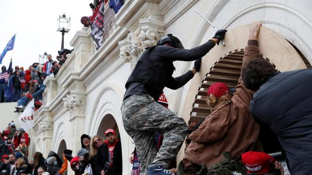 Pro-Trump protesters scale a wall as they storm the US Capitol Building, during clashes with Capitol police at a rally to contest the certification of the 2020 Presidential election results by the US Congress.(Reuters image)