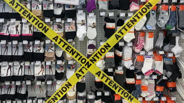 Tape is shown covering non-essential products that can't be sold at a pharmacy in Montreal, Quebec, Canada.(AP)
