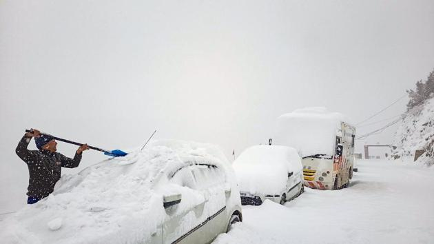 A man removes snow from a car after the town received fresh snowfall, at Keylong in Lahaul-Spiti District.(PTI)