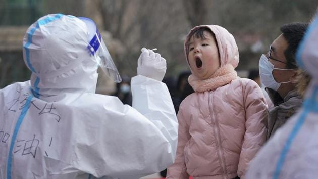 A medical staff in a protective suit prepares to take a swab from a child near a residential area in Shijiazhuang in north China's Hebei province.(AP)