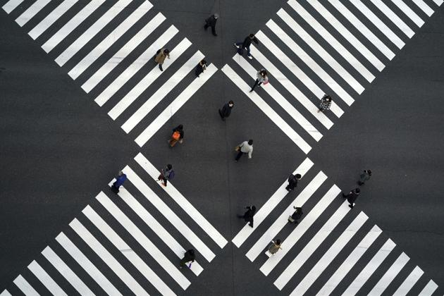 A thin crowd walks across pedestrian crossings in the Ginza shopping area of Tokyo, Japan on January 8. Japanese Prime Minister Yoshihide Suga has declared a state of emergency in Tokyo and three adjoining prefectures, after Covid-19 infections and the number of people in serious condition reached record levels. The measure has been imposed from January 8 to February 7. (Eugene Hoshiko / AP)