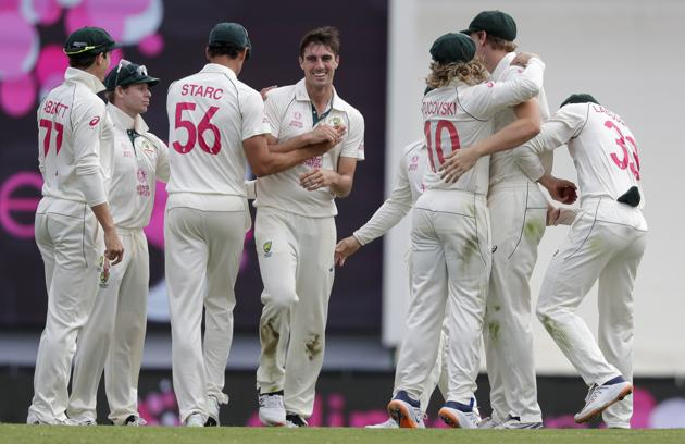 Australia's Pat Cummins, centre, is congratulated by teammates after dismissing India's Shubman Gill for 50 runs during play on day two of the third cricket test between India and Australia at the Sydney Cricket Ground, Sydney, Australia, Friday, Jan. 8, 2021. (AP Photo/Rick Rycroft) (AP)