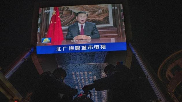 Security guards change shift under a screen showing Chinese President Xi Jinping delivering a speech for the evening news broadcast in Beijing on December 31.(AP file)