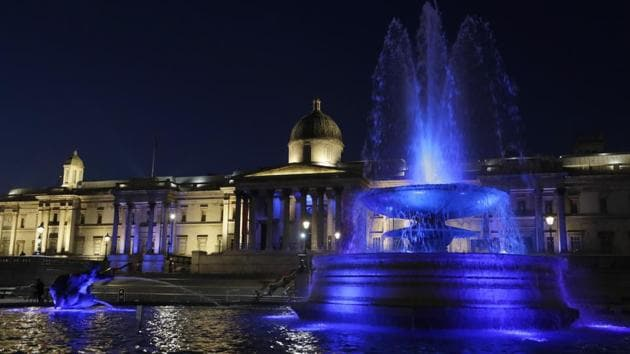 Fountains in Trafalgar Square are lit with blue lights to show support for the NHS in London, on January 7, 2021.(AP)