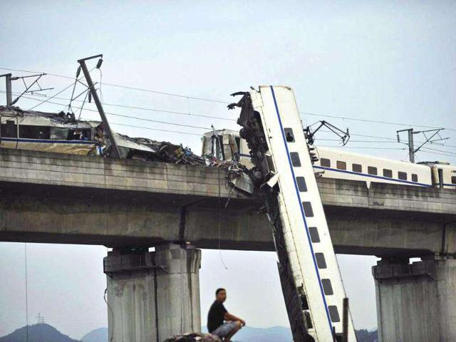 A-man-sits-by-the-wreckage-of-a-train-accident-in-Wenzhou-in-east-China-s-Zhejiang-province-A-Chinese-bullet-train-crashed-into-another-high-speed-train-that-had-stalled-after-being-struck-by-lightning-in-eastern-China-causing-four-carriages-to-fall-off-a-viaduct