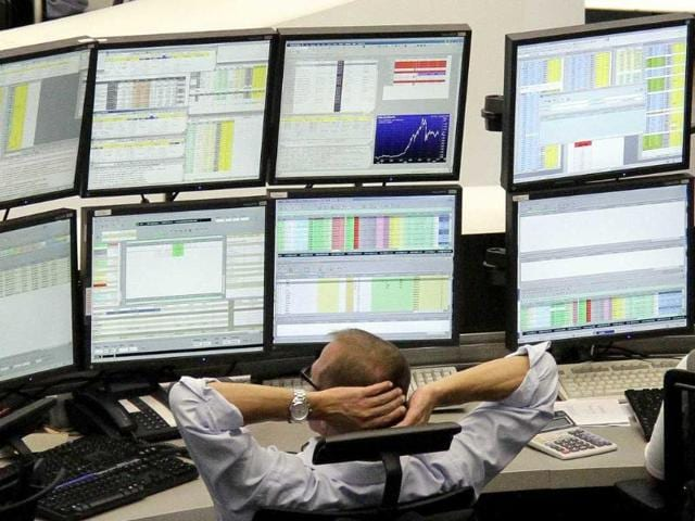 A-man-reacts-in-front-of-an-electronic-board-showing-stock-information-at-a-brokerage-house-in-Shanghai