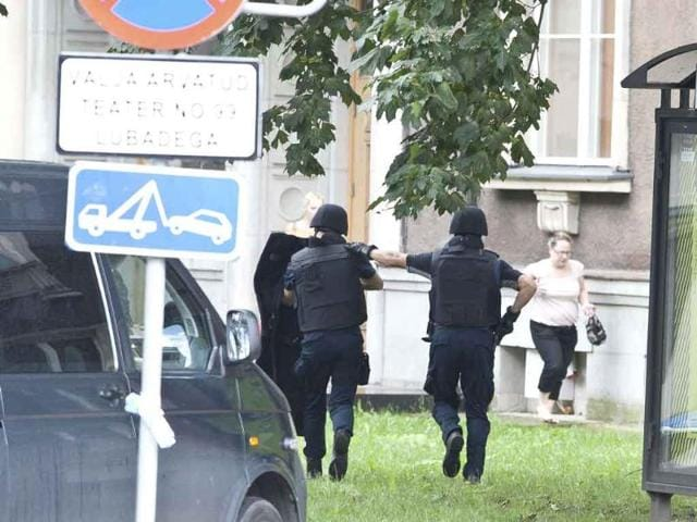 Estonian-police-officers-gesture-to-women-outside-the-building-of-the-defence-ministry-in-Tallinn