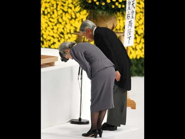 Japan's emperor Akihito (R) and empress Michiko bow before a huge bank of chrysanthemums to offer prayers for the war dead during a memorial service at Budokan in Tokyo.