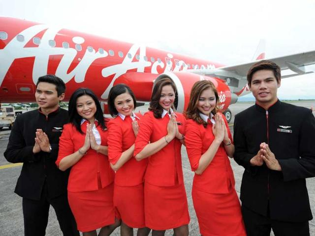 Cabin crew of AirAsia Philippines pose for photos next to an Airbus A320 shortly after arriving from Toulose in France at the former US military Clark air base in Angeles City, Pampanga province, north of Manila.