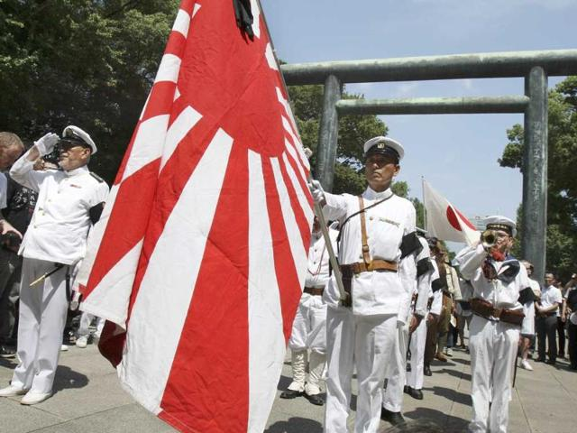 Men in Japanese Imperial navy uniforms stand at attention to pay their respects to the war dead at Yasukuni Shrine in Tokyo.