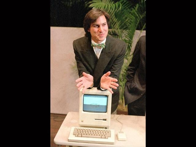 In 1984 file photo, Steve Jobs, chairman of the board of Apple Computer, leans on the new Macintosh personal computer following a shareholder