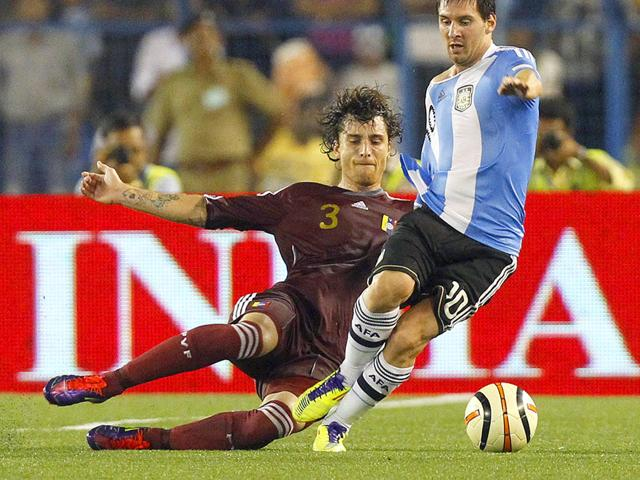 Argentina-s-Lionel-Messi-R-and-Venezuela-s-Fernando-Amorebieta-fight-for-the-ball-during-their-international-friendly-soccer-match-in-Kolkata
