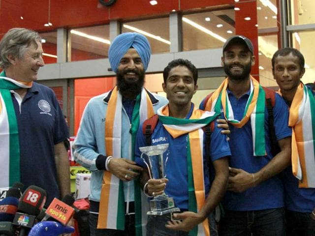 Indian-chief-hockey-coach-Michael-Nobbs-looks-on-as-players-pose-with-the-Asian-Champions-trophy