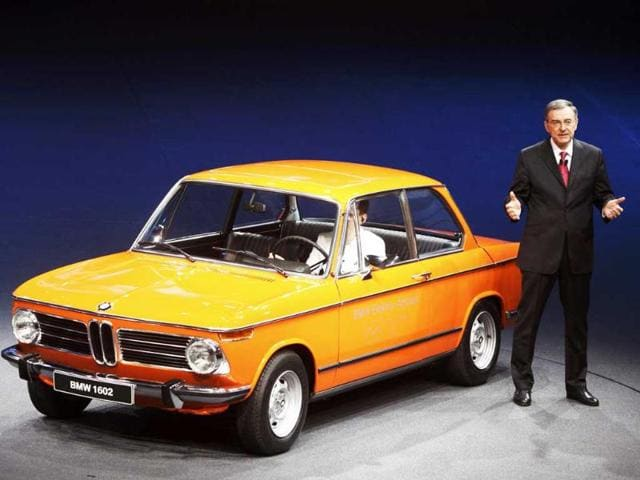 Chief Executive of German luxury carmaker BMW Norbert Reithofer poses next to a vintage BMW 1602 with an electric engine during the presentation of the 'BMW i3 Concept' and 'BMW i8 Concept' cars at the International Motor Show (IAA) in Frankfurt.