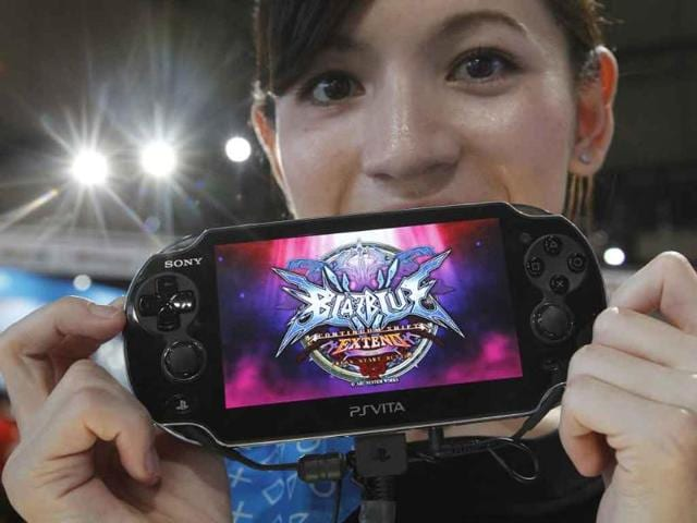 A-promotional-woman-shows-a--Sony-s-PlayStation-Vita-handheld-gaming-device-at-Tokyo-Game-Show-in-Chiba-east-of-Tokyo