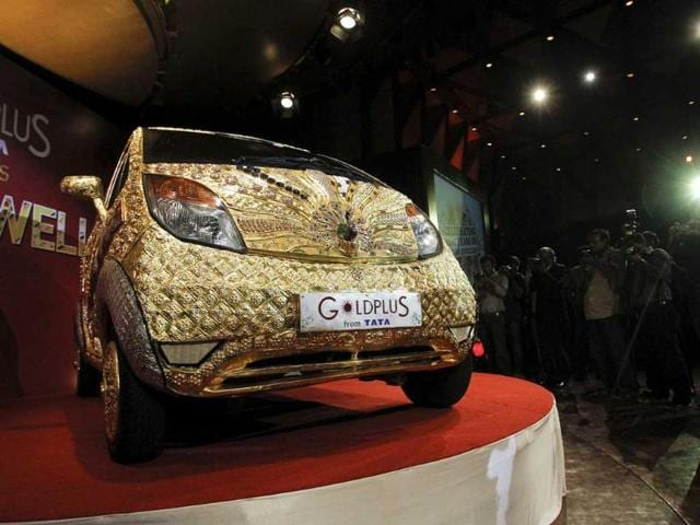 Photographers take pictures of a Tata Nano car made of gold during a ceremony in Mumbai. About 80 kg of 22 karat gold, approximately 15 kg of silver and gemstones were used to decorate the car, according to a press statement.