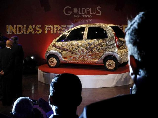 People watch the unveiling of a Tata Nano car made of gold during a ceremony in Mumbai. About 80 kg of 22 karat gold, approximately 15 kg of silver and gemstones were used to decorate the car, according to a press statement.
