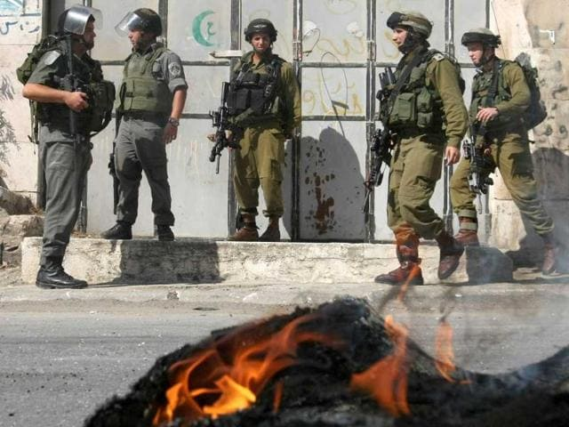 Israeli-soldiers-keep-watch-as-Palestinian-boys-burn-tires-and-throw-stones-close-to-an-Israeli-army-checkpoint-near-the-Jewish-settlers-zone-of-Abraham-Avino-in-the-centre-of-the-West-Bank-city-of-Hebron
