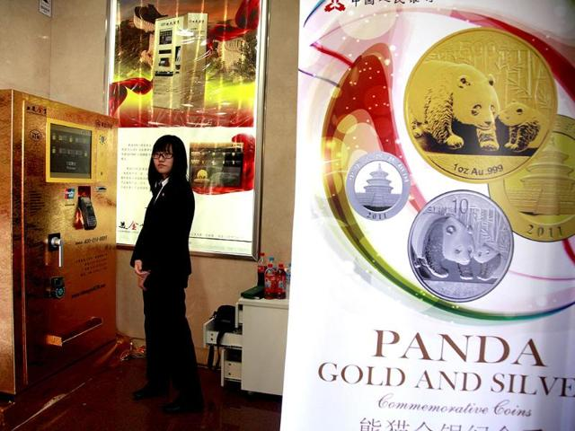 A-staff-member-waits-for-customers-to-try-out-the-gold-bar-dispensing-ATM-machine-set-up-in-Beijing