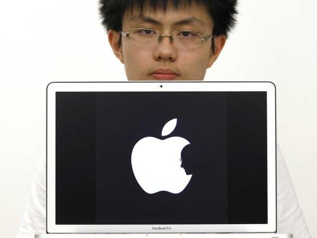 Hong-Kong-design-student-Jonathan-Mak-poses-with-a-symbol-he-designed-as-a-tribute-to-Apple-founder-Steve-Jobs-The-logo-became-an-internet-hit-with-its-minimalist-touching-symbolism-and-brought-a-job-offer-and-a-flood-of-commemorative-merchandise-using-his-design