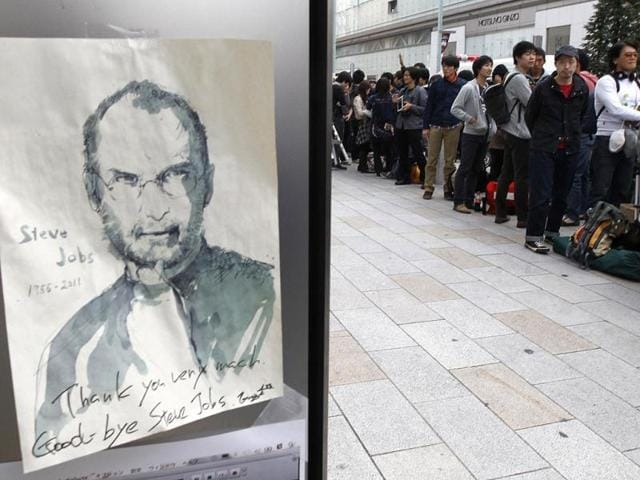 An-image-commemmorating-Apple-co-founder-Steve-Jobs-is-seen-near-customers-queueing-to-buy-iPhone-4S-outside-an-Apple-shop-in-Tokyo