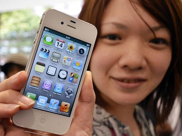 A-customer-holds-up-her-newly-bought-Apple-iPhone-4S-on-the-day-of-its-release-outside-a-Softbank-shop-in-Tokyo