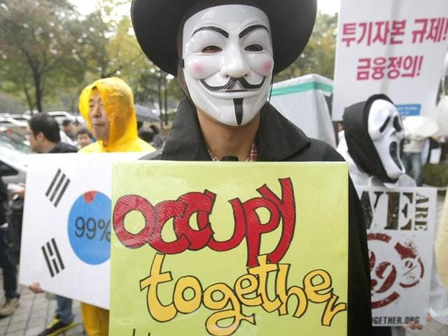 Protesters-wearing-Guy-Fawkes-masks-made-popular-by-the-graphic-novel-V-for-Vendetta-take-part-in-the-Occupy-central-protest-outside-the-Hong-Kong-Stock-Exchange