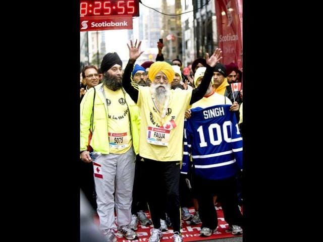 Fauja-Singh-100-center-celebrates-at-the-finish-line-after-completing-the-Toronto-Waterfront-Marathon-in-Toronto-on-Sunday