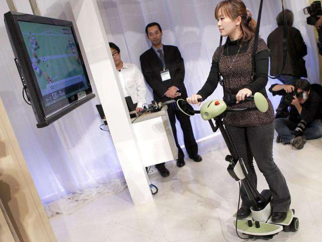 A Toyota Motor Corp. staff plays a TV soccer game as she demonstrates a 'balance training assist' robot during a Toyota event displaying experimental hi-tech health care robots at a Toyota showroom in Tokyo.
