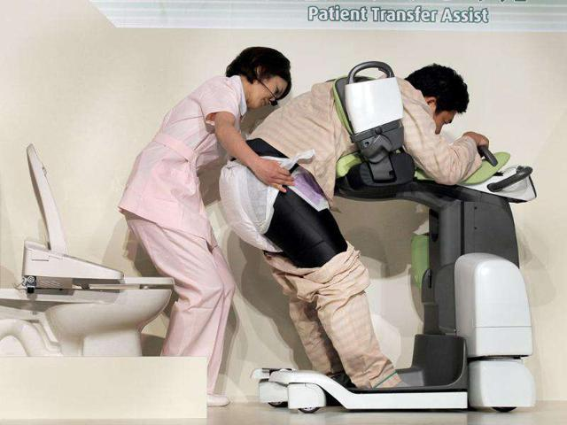 A Toyota Motor Co. staff playing a patient's roll is assisted by a Fujita Health University Senior Assistant Prof. Yukari Suzuki as they demonstrate a 'patient transfer assist' robot.