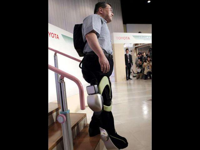 Eiichi Saitoh, a professor in rehabilitation medicine, steps down with an 'independent walk assist' device as Toyota Motor Corp. displays experimental health care robots at a Toyota showroom in Tokyo.