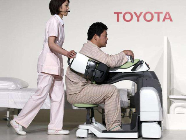 A man acting as a patient is transported by a 'Patient Transfer Assist' robot, developed to reduce the heavy physical burden required for caretakers when transferring patients.