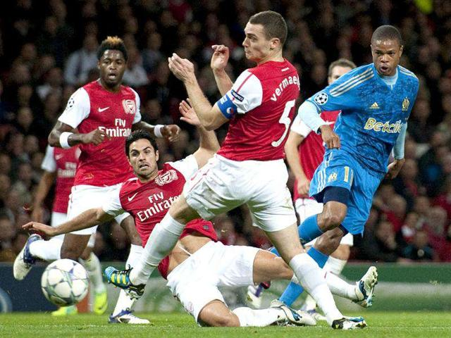 Olympique-de-Marseille-s-Loic-Remy-R-shoots-past-Arsenal-s-Mikel-Arteta-2nd-L-and-Thomas-Vermaelen-C-during-the-UEFA-Champions-League-Group-F-match-at-The-Emirates-stadium-in-London