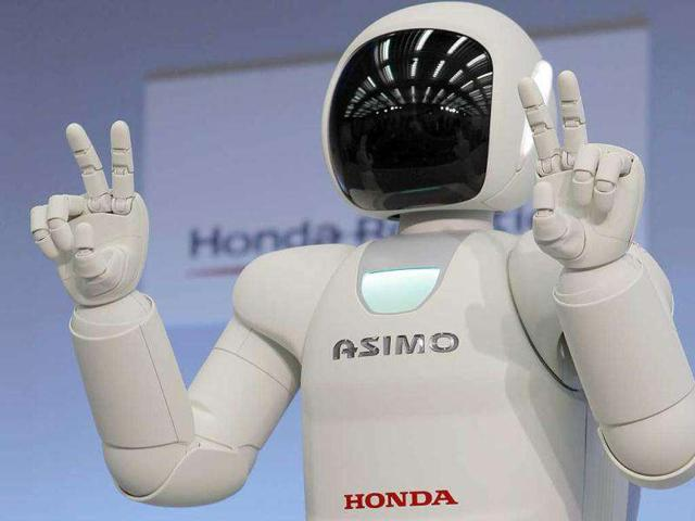 Honda-Motor-Co-s-revamped-human-shaped-robot-Asimo-uses-a-Japanese-sign-language-during-a-news-conference-at-the-Japanese-automaker-s-research-facility-in-Wako-near-Tokyo-Asimo-can-now-run-faster-balance-itself-on-uneven-surfaces-hop-on-one-foot-pour-a-drink-and-even-almost-think-on-its-own