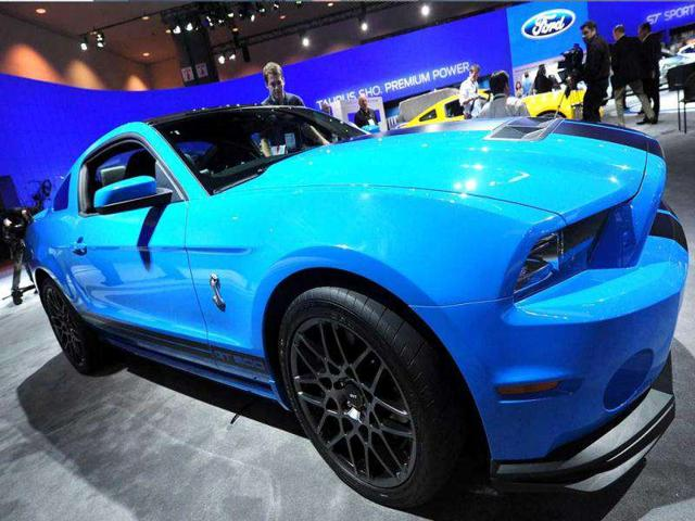 A man steps into a Ford Shelby Cobra GT500 on display at the 2012 Los Angeles Auto Show.