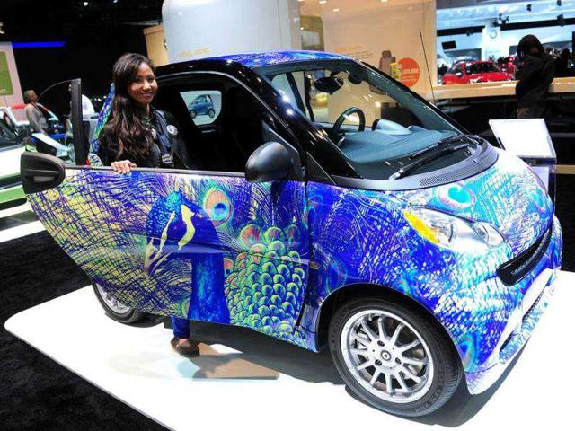 The model behind the passenger door of a Smart Fortwo Coupe on display at the 2012 Los Angeles Auto Show.