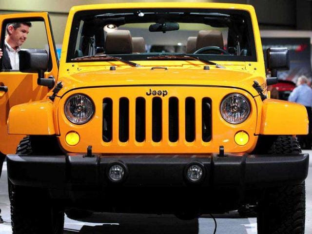 A man opens the passenger door of a Jeep Wrangler on display at the 2012 Los Angeles Auto Show.