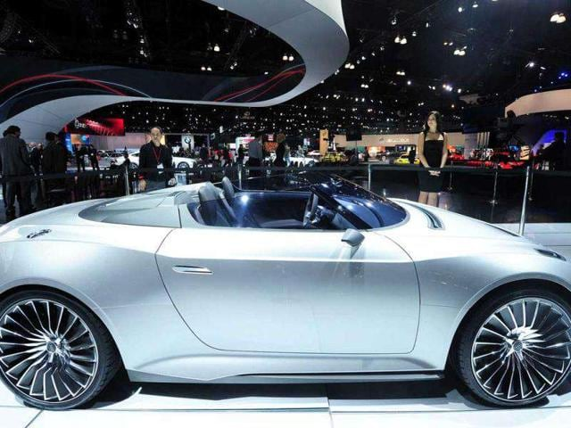 A model stands behind a diesel-electric Audi e-tron Spyder roadster on display at the 2012 Los Angeles Auto Show.