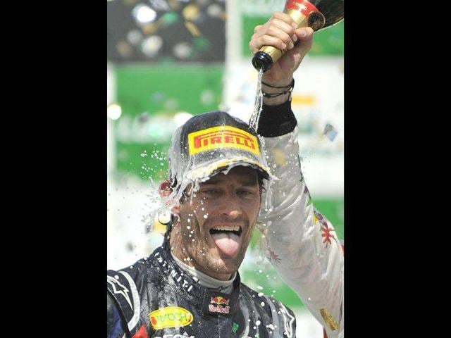 British-F-1-driver-Jenson-Button-of-McLaren-out-of-the-picture--sprays-champagne-on-Australian-Mark-Webber-L-of-Red-Bull--on-the-2011-Brazilian-Formula-1-GP-podium-ceremony-at-the-Interlagos-racetrack-Sao-Paulo-Brazil-Webber-won-the-race-and-qualified-second-in-the-World-Championship-whilst-Vettel-arrived-second-in-the-race-and-is-the-2011-champion--AFP-PHOTO-NELSON-ALMEIDA