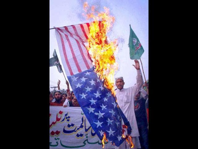 Supporters-from-religious-political-party-Sunni-Tehreek-who-are-demonstrating-against-a-Nato-cross-border-attack-burn-the-US-flag-in-Lahore