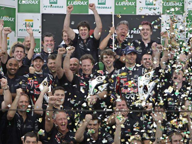 Surrounded-by-members-of-their-team-Red-Bull-drivers-Sebastian-Vettel-of-Germany-center-row-center-left-and-Mark-Webber-of-Australia-center-row-center-right-hold-trophies-as-they-celebrate-at-the-end-of-the-Brazilian-Formula-One-Grand-Prix-at-the-Interlagos-race-track-in-Sao-Paulo-Brazil-Webber-won-the-race-and-Vettel-finished-second-place-AP-Photo-Andre-Penner