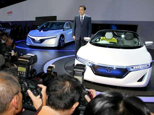 Honda Motor Co. president Takanobu Ito poses for photo with the company's concept car 'AC-X' at the press conference during the press preview of Tokyo Motor Show in Tokyo.