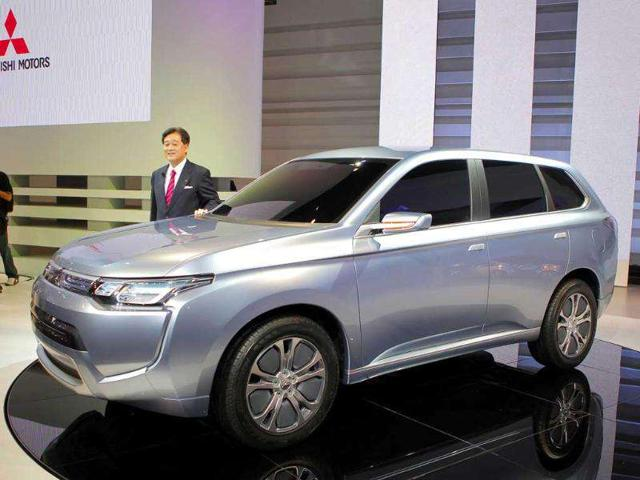 Mitsubishi Motors Corp. president Osamu Masuko poses with concept car 'PX MIE2' during the press preview of Tokyo Motor Show in Tokyo.