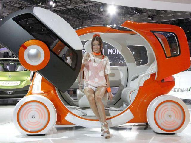 A model sits on Suzuki Motor Corp's concept car 'Q-Concept' during the press preview of Tokyo Motor Show in Tokyo.