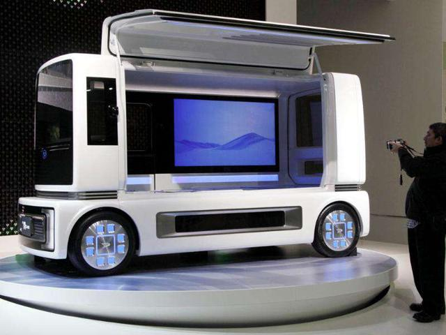 A visitor snaps Daihatsu Motor Co., concept car 'FC SHO CASE' on displays during the Tokyo Motor Show in Tokyo.