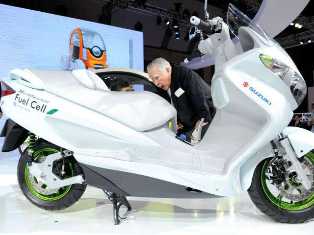 Osamu Suzuki, chairman of Japan's Suzuki Motor, inspects the company's fuel cell motorcycle called 'Burgman' during the Tokyo Motor Show in Tokyo.