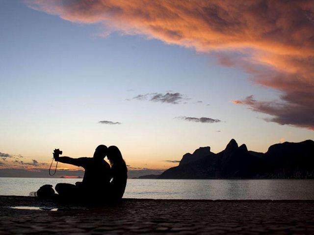 A-couple-takes-a-photograph-after-sunset-at-the-Arpoador-beach-in-Rio-de-Janeiro-Brazil