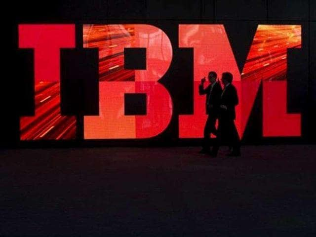 Two-men-walk-past-an-IBM-logo-in-Hanover-central-Germany
