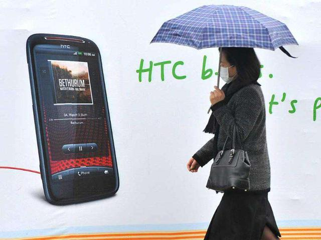 A-woman-walks-past-a-billboard-displaying-a-handset-of-Taiwan-smartphone-maker-HTC-in-Taipei-Apple-scored-a-hit-in-an-ongoing-patent-brawl-with-HTC-with-a-US-trade-authority-ruling-the-iPhone-maker-has-rights-to-features-using-one-tap-screen-commands