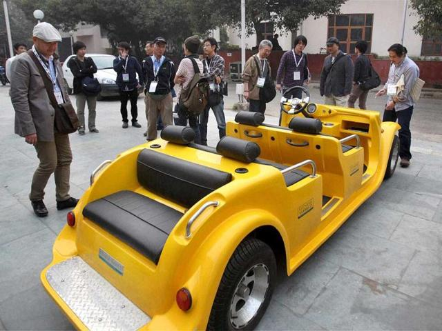 Chinese visitors having a look of a battery-operated car ahead of the Auto Expo 2012 at Pragati Maidan in New Delhi. PTI Photo/Manvender Vashit